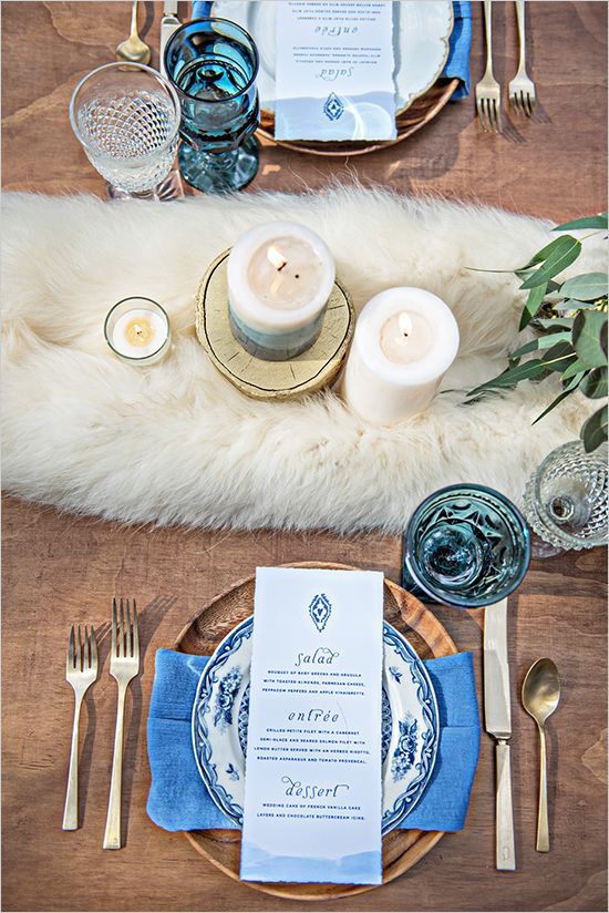 a white faux fur table runner, wooden chargers, blue glasses and napkins are great to make the tablescape chic and textural