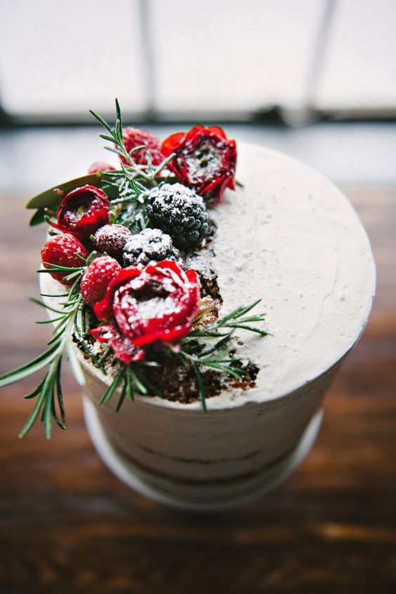 red blooms, evergreens, blackberries and foliage with sugar powder create a feeling of snowy items on your cake