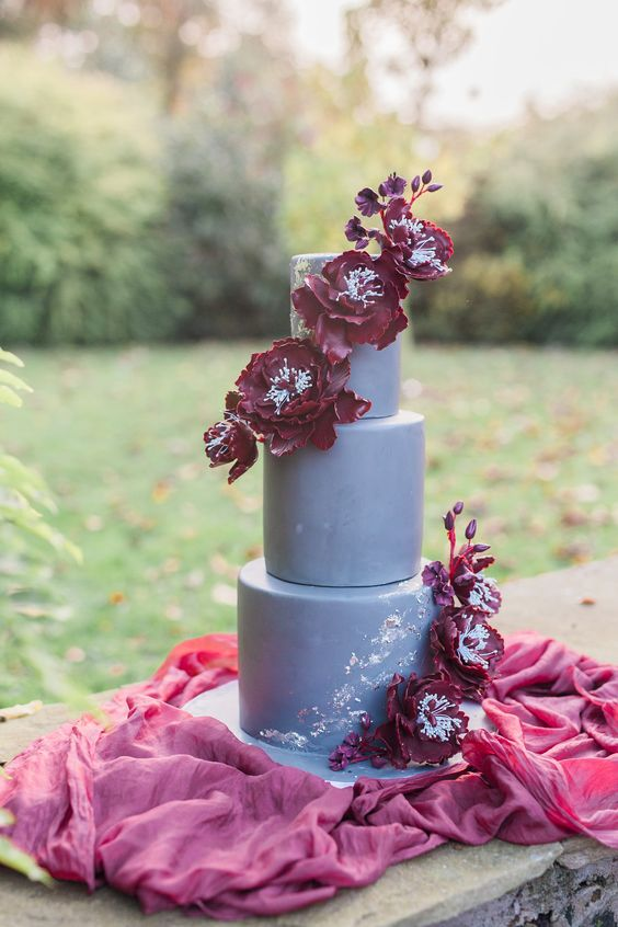 a fantastic matte grey wedding cake with burgundy sugar blooms and silver leaf looks wow