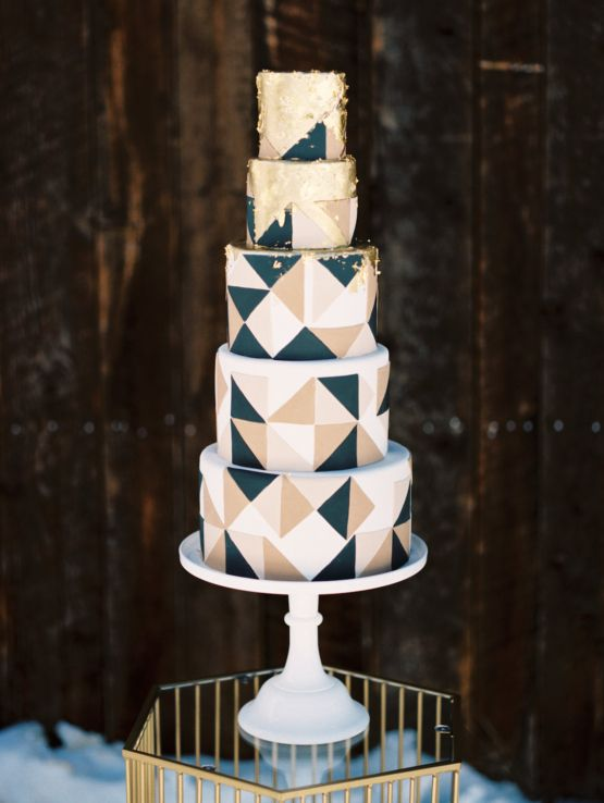 a modern geometric wedding cake with white, beige and black triangles and gold leaf on top to combine two trends in one