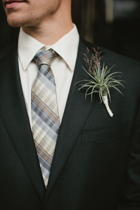 a chic boutonniere with an air plant and herbs for a touch of color and texture for a bold look
