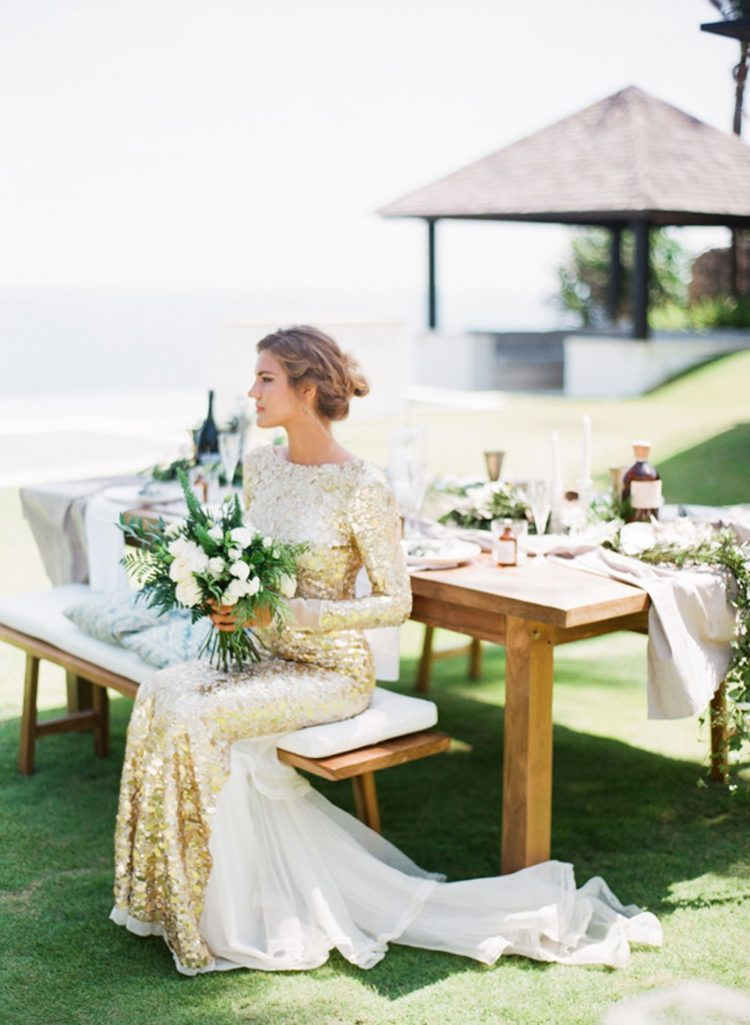 a gold sheath wedding dress with long sleeves, a high neckline and a white tille tail for a statement