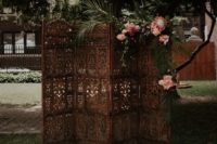 24 a vintage wood carve boho screen decorated with blooms and tropical leaves plus a boho rug for a boho chic ceremony