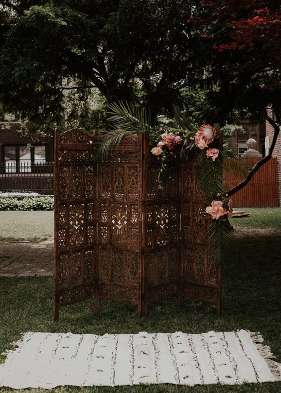 a vintage wood carve boho screen decorated with blooms and tropical leaves plus a boho rug for a boho chic ceremony