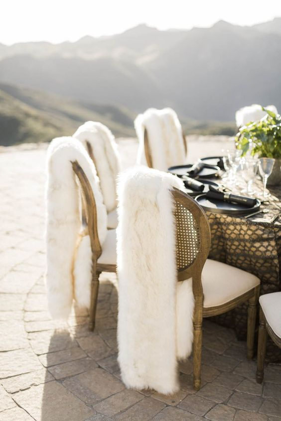 raise your chair decor to a new level covering them with faux fur, which will also keep your guests warm and comfy