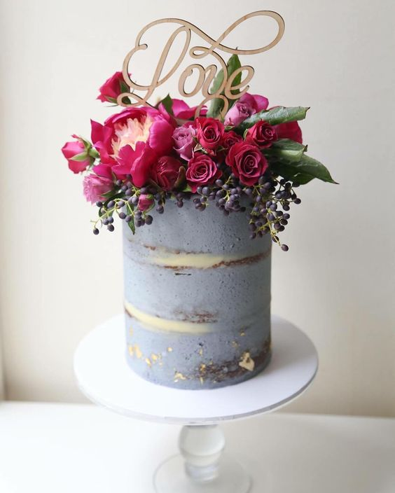 a semi naked greyish wedding cake topped with fuchsia and burgundy blooms, berries and a calligraphy topper