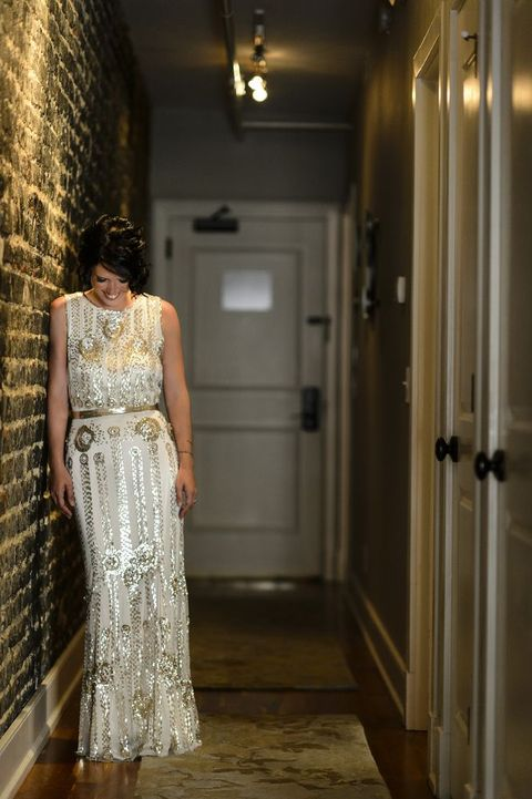 a sparkly white and gold embellishments art-deco wedding dress with a gold sash for a bright look