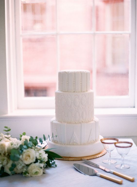 an all white wedding cake with unique frosting textures, all different for each tier is a modern and fresh idea