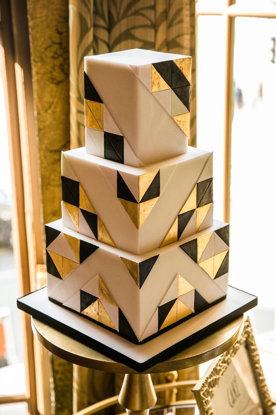 an art deco inspired wedding cake with white, black and gold triangles on white is a chic idea to rock