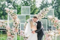 26 mesh frames for forming a backdrop, which is decorated with pink, white and blush florals for a glam feel