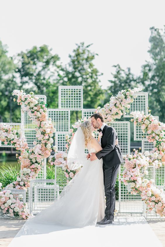 mesh frames for forming a backdrop, which is decorated with pink, white and blush florals for a glam feel