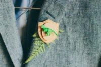 27 a whimsy boutonniere of leather and a little green dinosaur figurine plus fern for a wedding with dinosaur touches