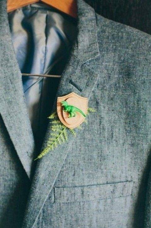 a whimsy boutonniere of leather and a little green dinosaur figurine plus fern for a wedding with dinosaur touches