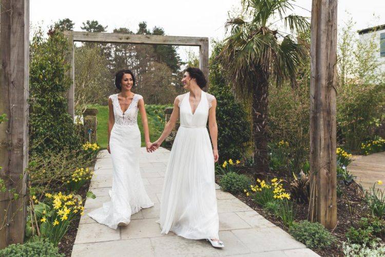 One bride was wearing a vintage lace wedding gown with a V-neckline, the other chose a Grecian-style dress with illusion cap sleeves and a simple neckline