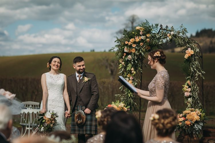 The wedding arch was a metal one lushly decorated with greenery and peachy and blush roses