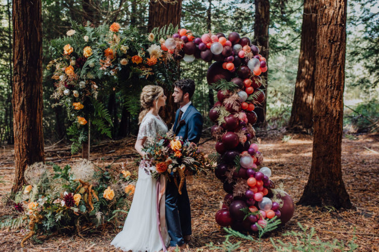 There was a gorgeous fall wedding arch of lush and bright florals, bold balloons and herbs around