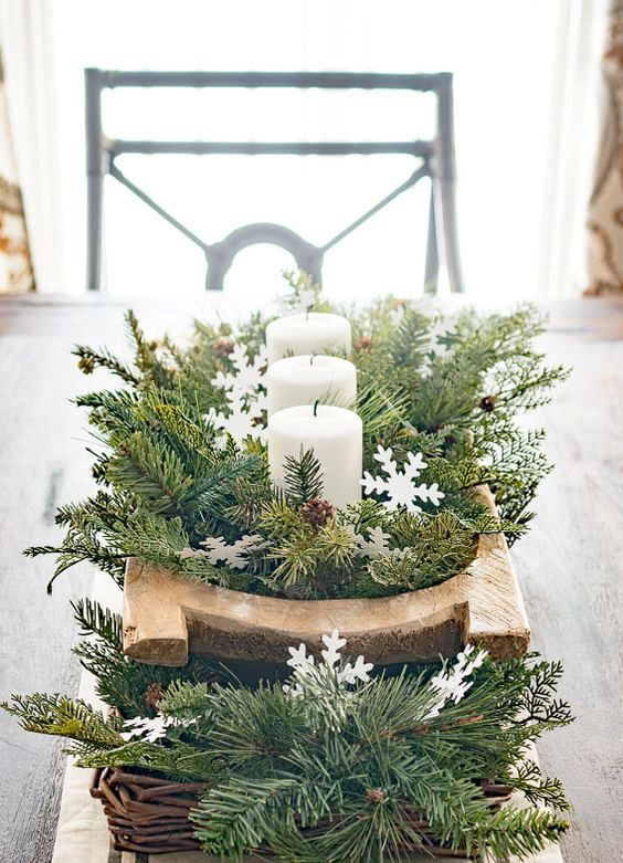 a beautiful winter wedding centerpiece of a basket with evergreens and a breadbowl with evergreens and candles plus pinecones and snowflakes