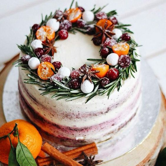 a buttercream wedding cake with citrus, berries and evergreens is a fresh take on traditional Christmassy cakes