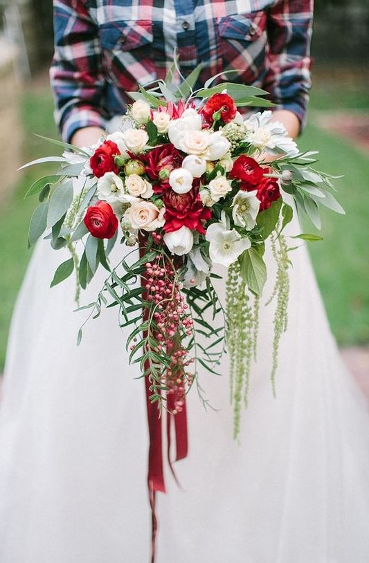 a cascading Christmas wedding bouquet of red and white blooms, foliage and berries and bright ribbons