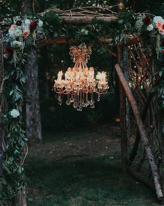 a gorgeous wild boho wedding arch of branches, foliage, bright blooms and with a glam chandelier to light up the space