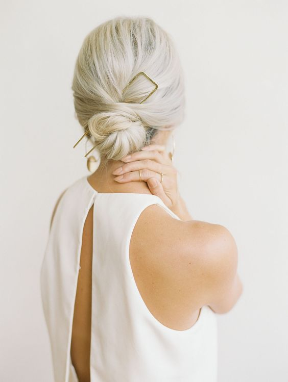 a low bun with a bump and an oversized gilded accessory is ideal for a minimalist bride