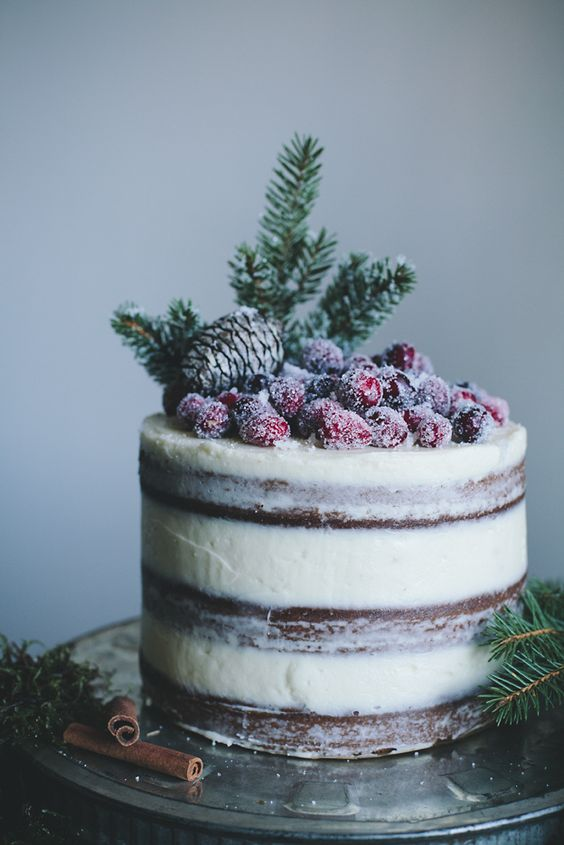 a soft gingerbread cake with cream cheese frosting and sugared cranberries, pinecones and evergreens