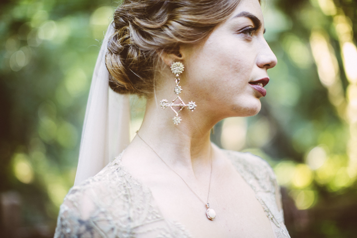 The bride was rocking statement earrings and a chic twisted updo plus a dark lip