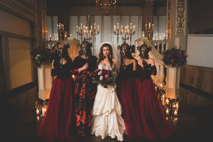 The bridesmaids were wearing burgundy ballgowns with velvet corsets and masks instead of bouquets