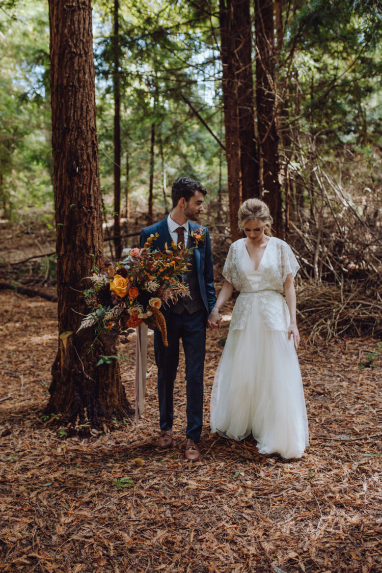 The groom was wearing a navy suit with a burgundy tie, a brown waistcoat and brown shoes