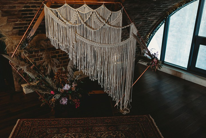 The wedding backdrop was a copper tube hexagon with a macrame hanging, lush blooms, dried herbs and pampas grass