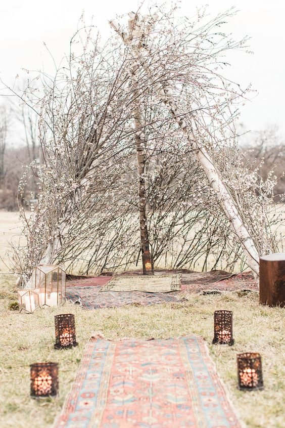 a beautiful tipi made of cherry blossom with rugs and lanterns around is amazing for a Nordic spring ceremony