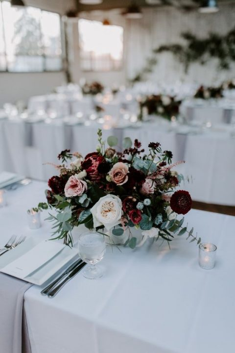 a bright and a bit moody winter floral centerpiece with burgundy, blush and white blooms and pale greenery