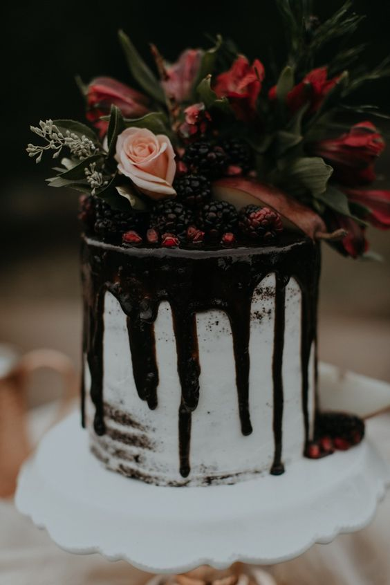 a chic naked drizzle wedding cake topped with berries and dark blooms and foliage for Christmas