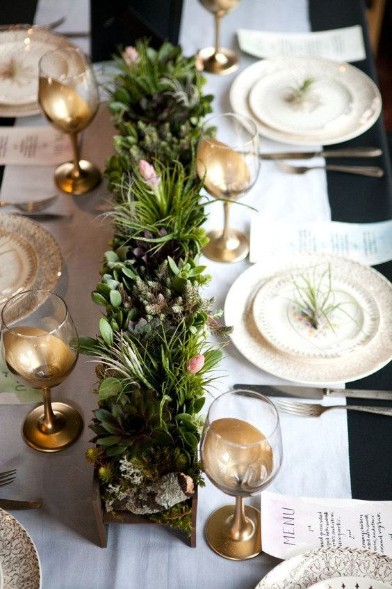 a cute and natural centerpiece of a wooden box with moss, evergreens, succulents and little blooms for a winter or Christmas wedding