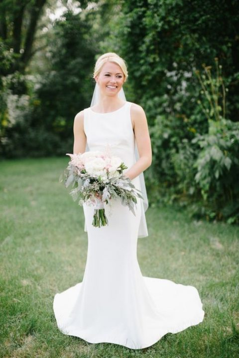 a sleeveless high neckline fitting wedding dress with a train plus a veil for create a chic modern bridal look