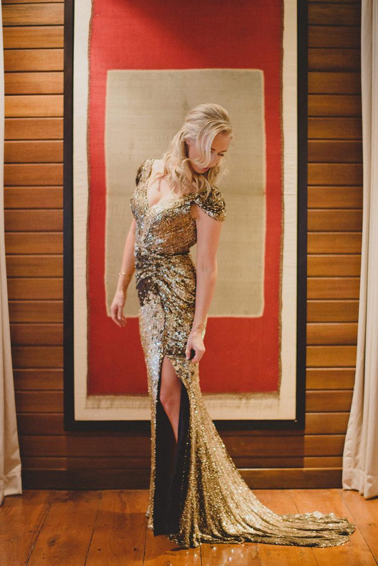 a super elegant gold sheath wedding dress with a deep V neckline, cap sleeves and a side slit for a glam feel