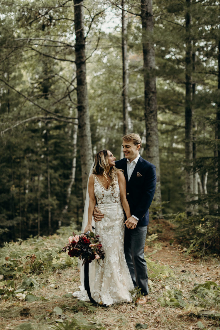 The bride was wearing a lace applique sleeveless fitting wedding dress with a deep V-neckline and a veil, the groom was rocking grey pants, a navy blazer and brown shoes