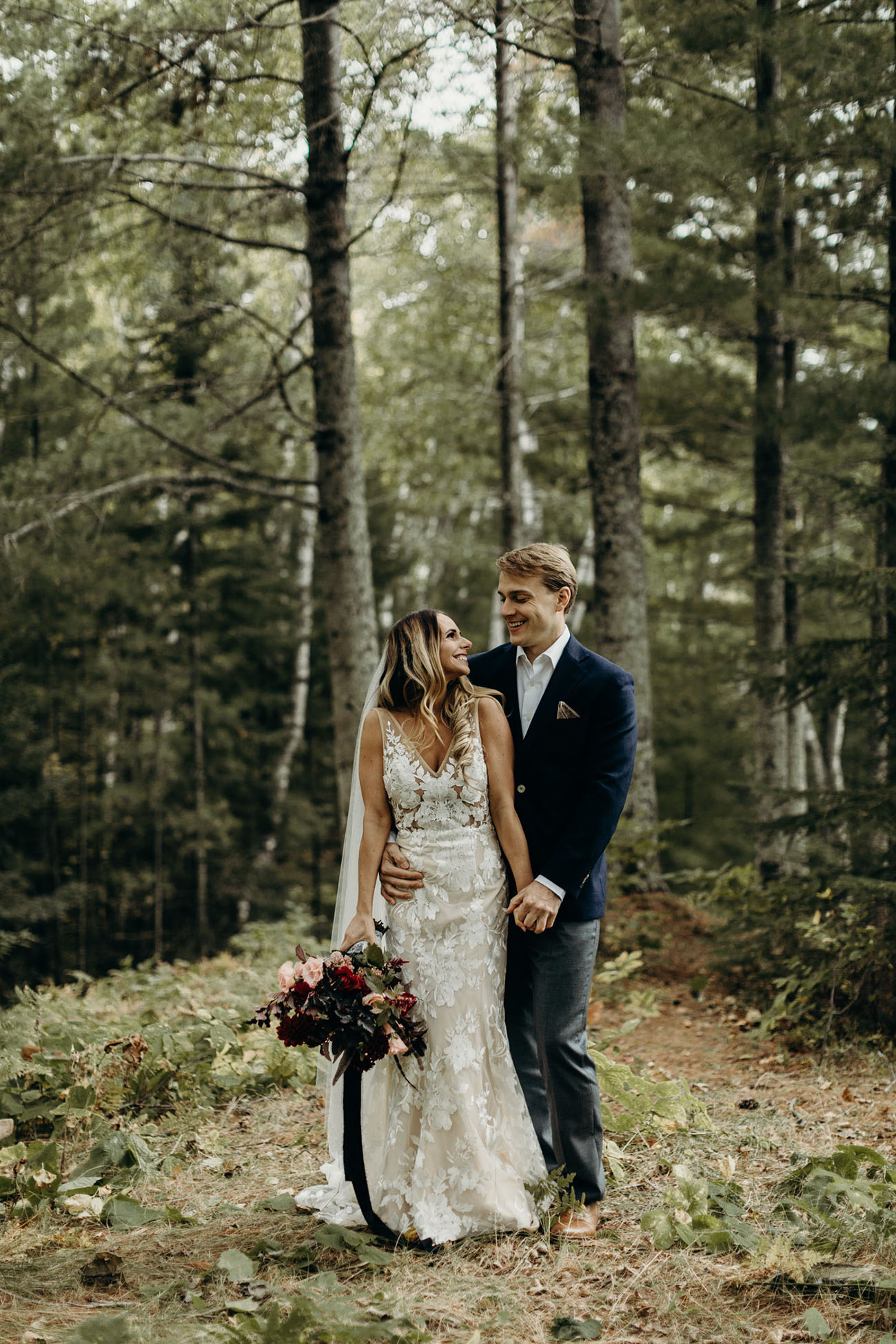 The bride was wearing a lace applique sleeveless fitting wedding dress with a deep V neckline and a veil, the groom was rocking grey pants, a navy blazer and brown shoes