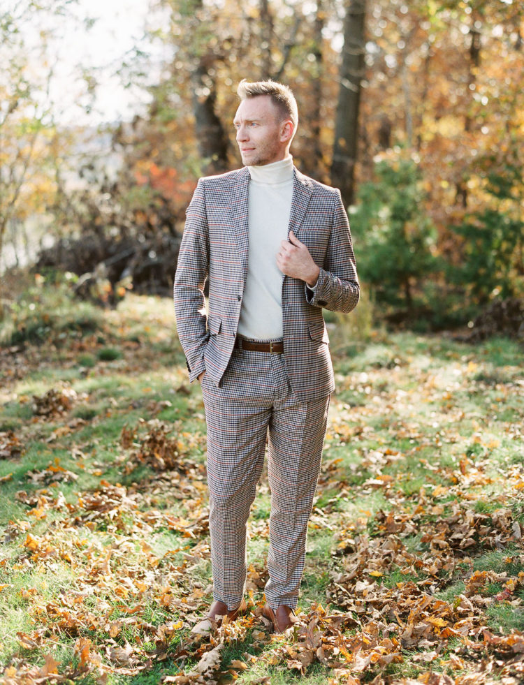 The groom was wearing a plaid suit, a neutral turtleneck and brown shoes