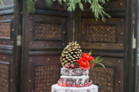 04 a bark-imitating wedding cake with cranberries, red blooms and a large pinecone on top is chic for a Christmas celebration