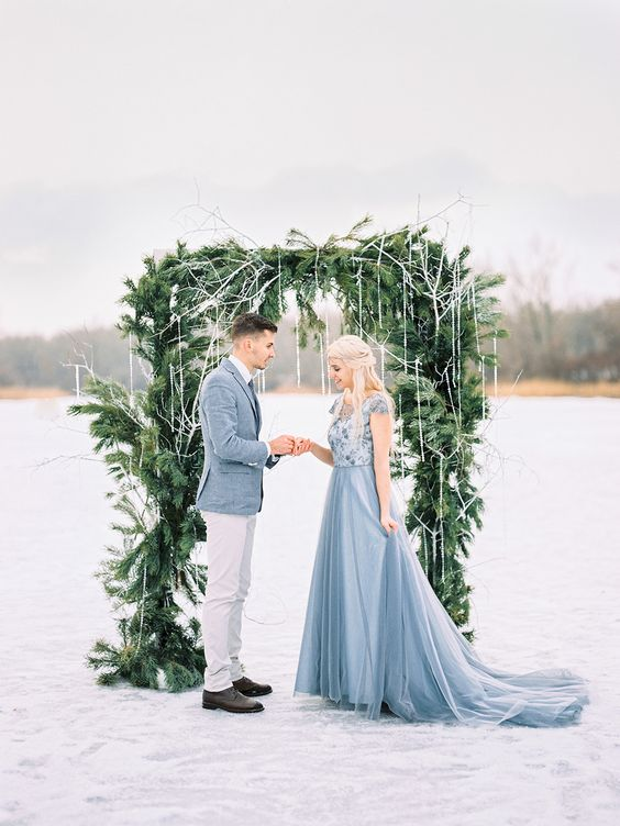 a beautiful winter wedding arch of evergreens with fake icicles hanging gown for a frozen feel