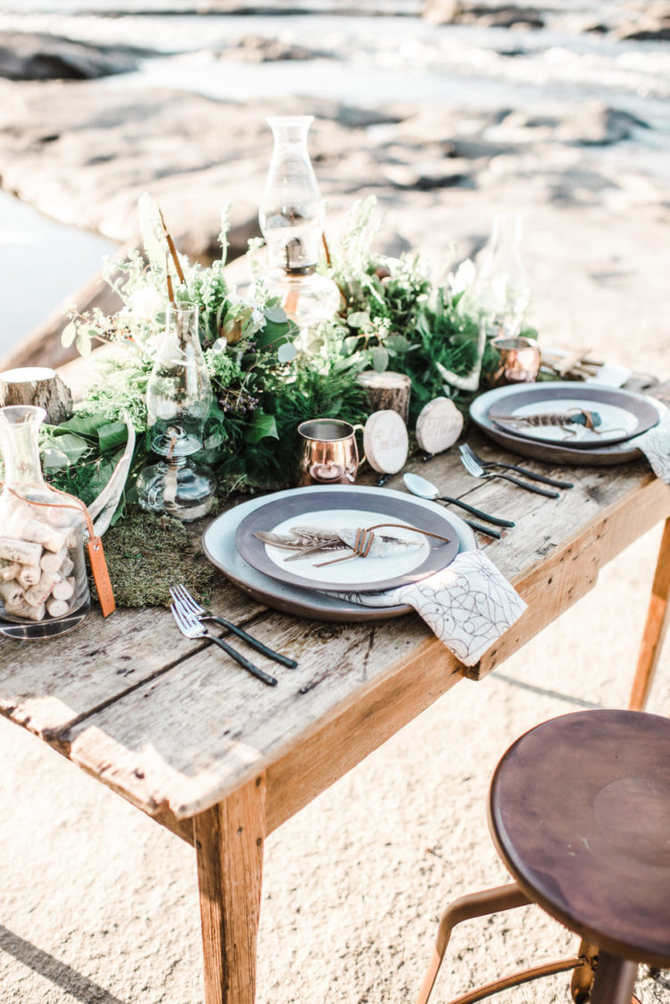a gorgeous textural greenery wedding centerpiece with little stumps, moss, antlers and an oil lamp for a woodland or nature-inspired wedding