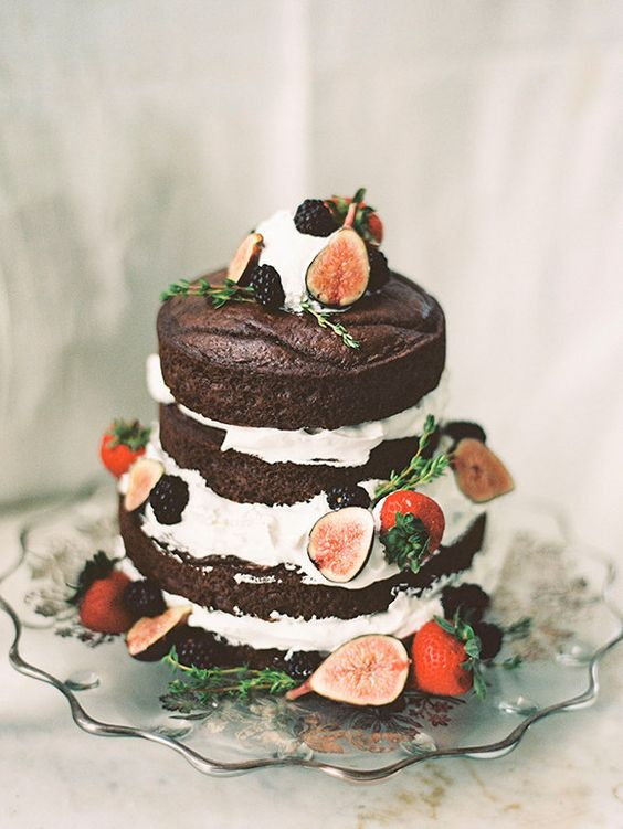 a naked chocolate wedding cake with blackberries, figs, straberries and much frosting looks super yummy