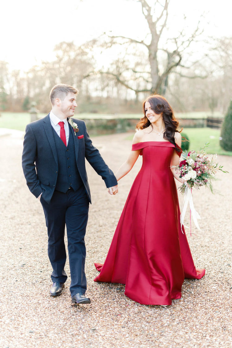 a red off the shoulder A line wedding gown with a train is a gorgeous statement