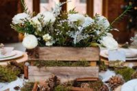 04 a rustic wedding centerpiece of a crate on moss, with pinecones and cinnamon bark, with white blooms and evergreens