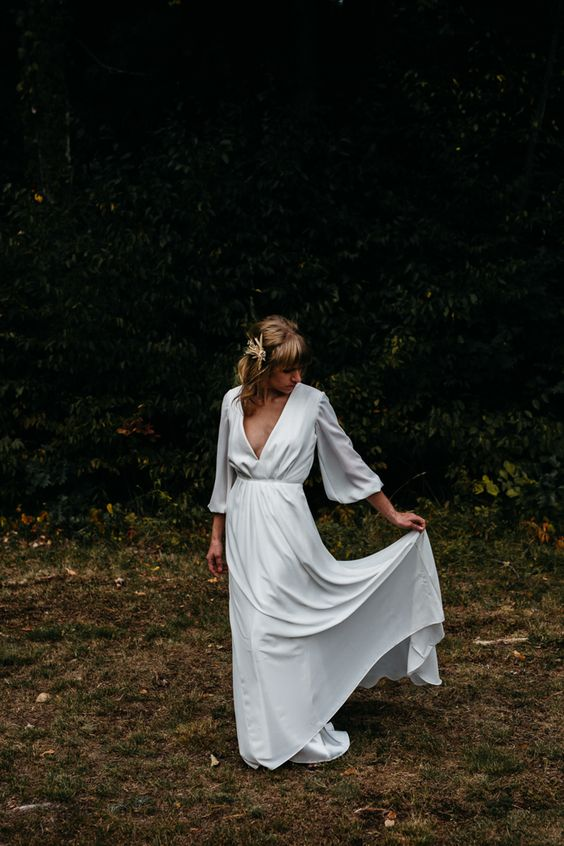 an ultra-minimalist plain wedding dress with a highlighted waist, wide bell sleeves and a plunging neckline
