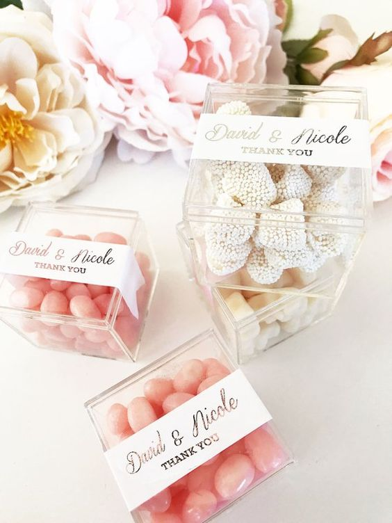 various candies packed into acrylic boxes with tags are a timeless favor for any wedding