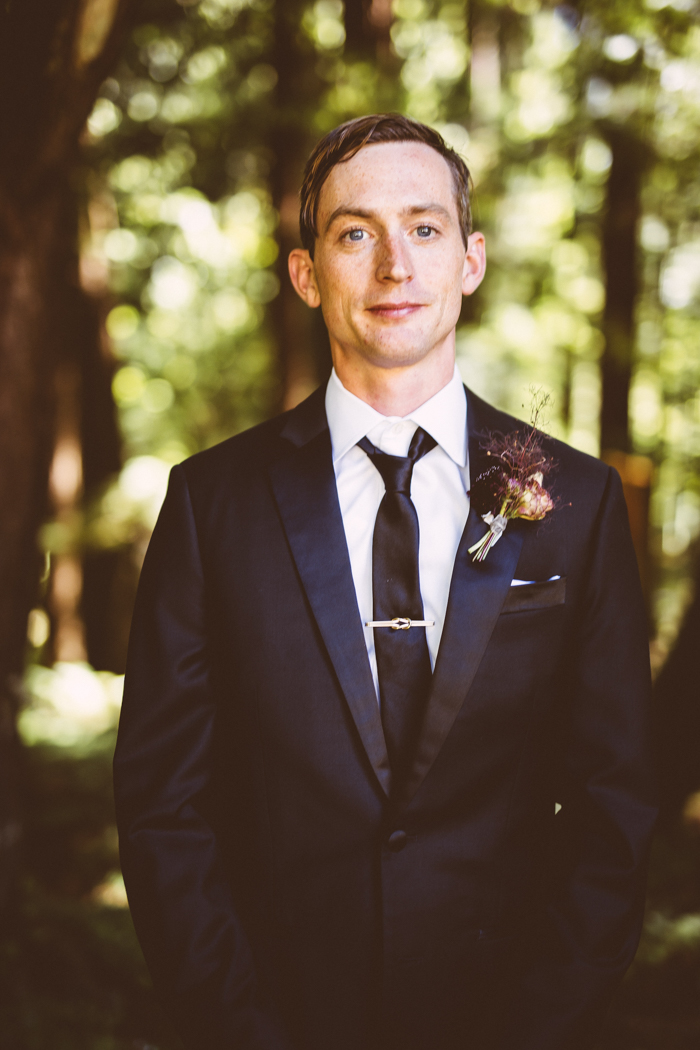 The groom was rocking a black suit with a black tie and a floral boutonniere with herbs