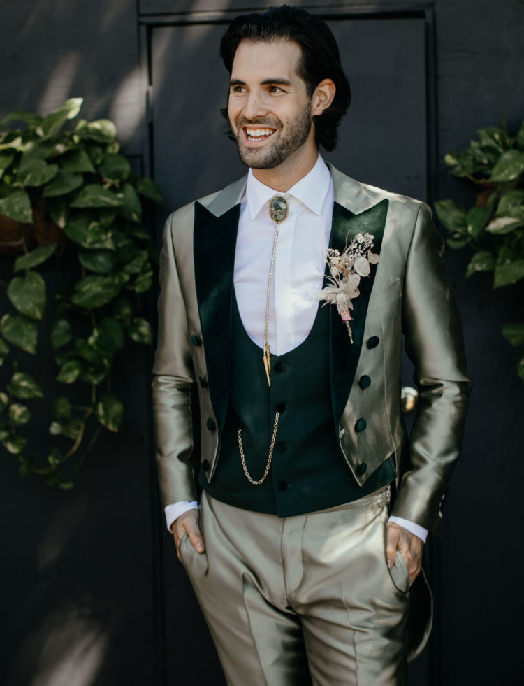 The groom was wearing a green custom made three-piece suit with a bejeweled tie