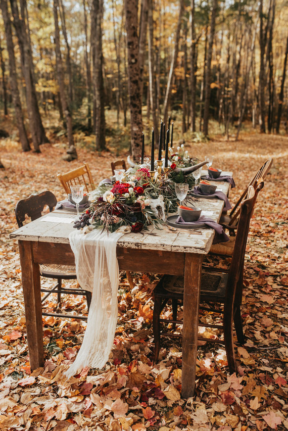 The wedding reception was moved to the forest, there were lush florals, an airy table runner, black candles and mismatched chairs